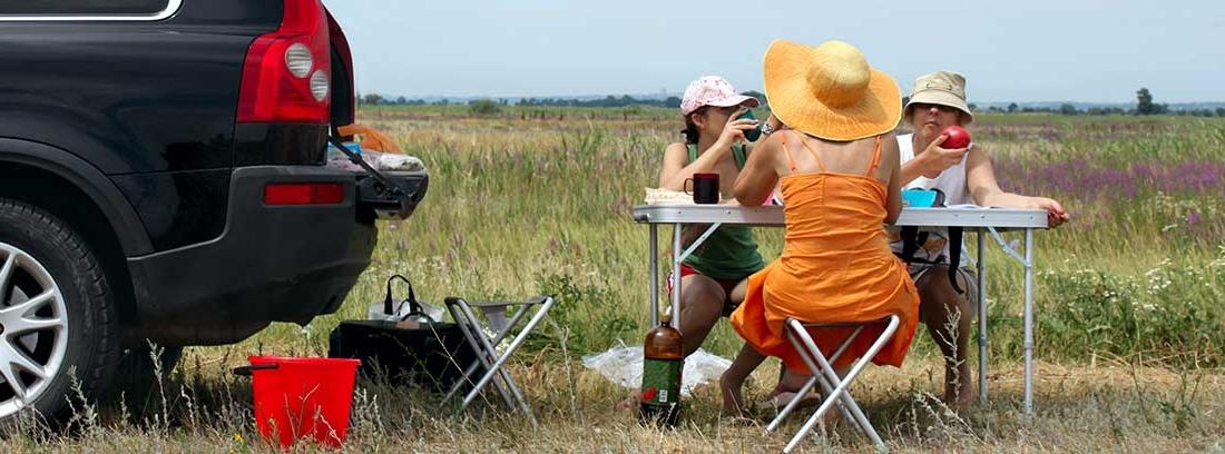 mesa de camping junto a un vehículo