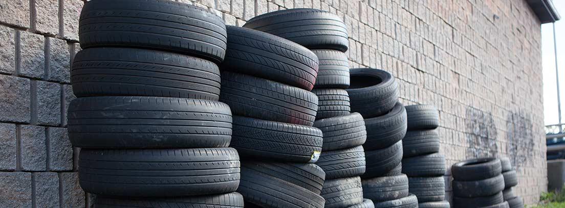 Varios neumáticos apilados contra una pared