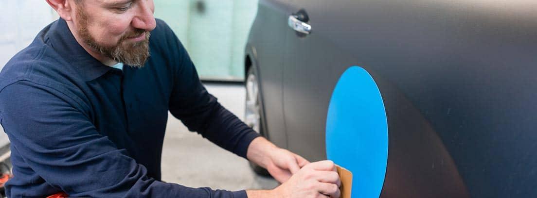 Hombre agachado poniendo una pegatina con un círculo azul en un coche negro