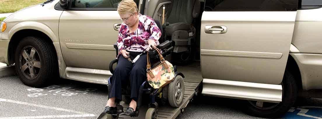 Mujer en silla de ruedas bajando de un coche adaptado