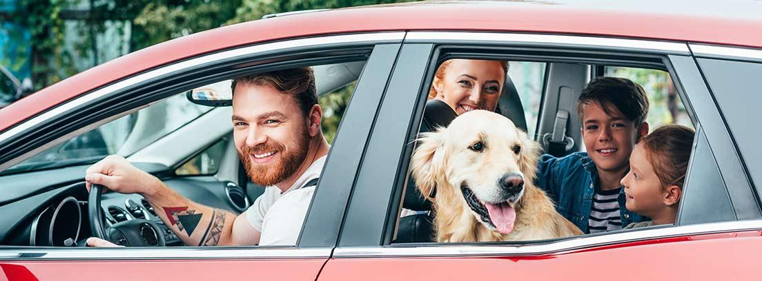 Coche rojo con familia con perro dentro