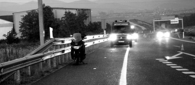 una moto aparcada en el arcén con una furgoneta detrás
