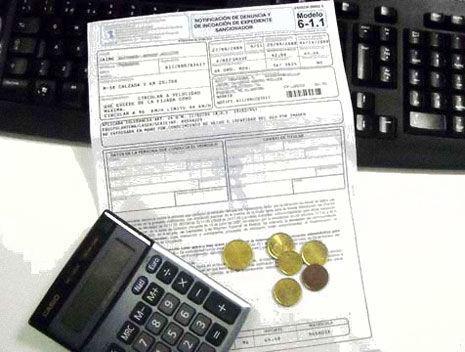 Una multa de tráfico sobre un teclado con monedas y calculadora