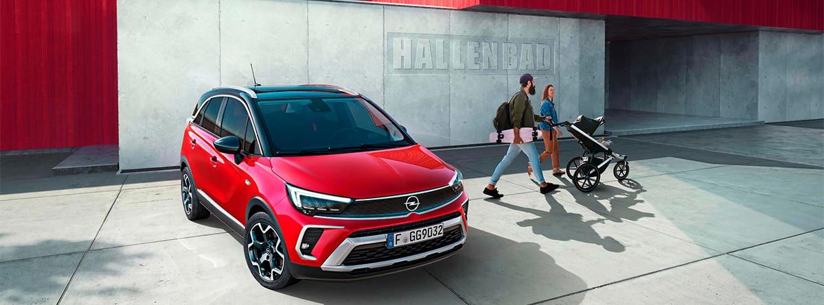 Pareja con coche de bebé junto a un Opel Crossland