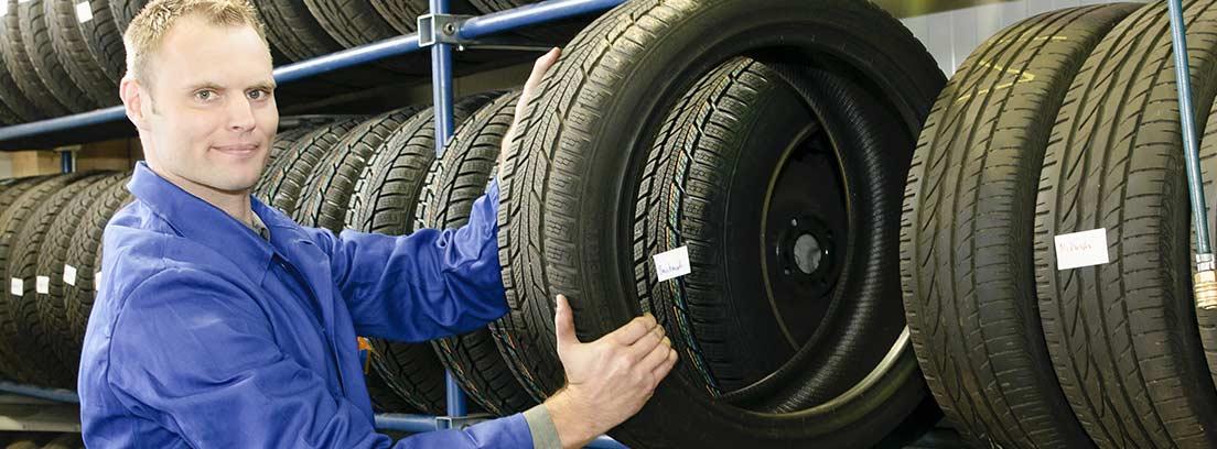 Hombre mostrando un neumático de una estantería