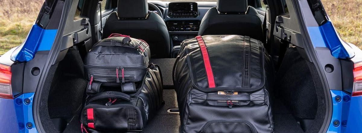 Maletero abierto del nuevo Nissan Qashqai 2021 azul con maletas dentro y los asientos traseros abatidos