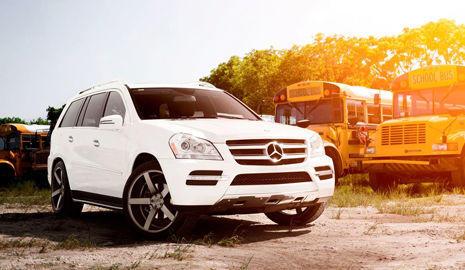 un Mercedes todoterreno aparcado alrededor de autobuses de escuela