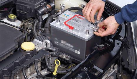 Mecánico realizando el mantenimiento de la batería del coche