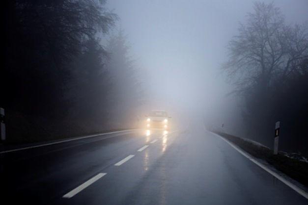 Coche con antiniebla delantero encendidos por una carretera con mucha niebla.