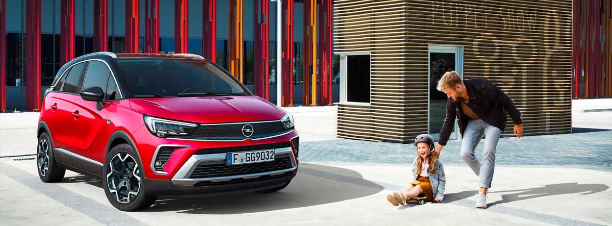Opel Crossland X rojo junto a un hombre y una niña con monopatín