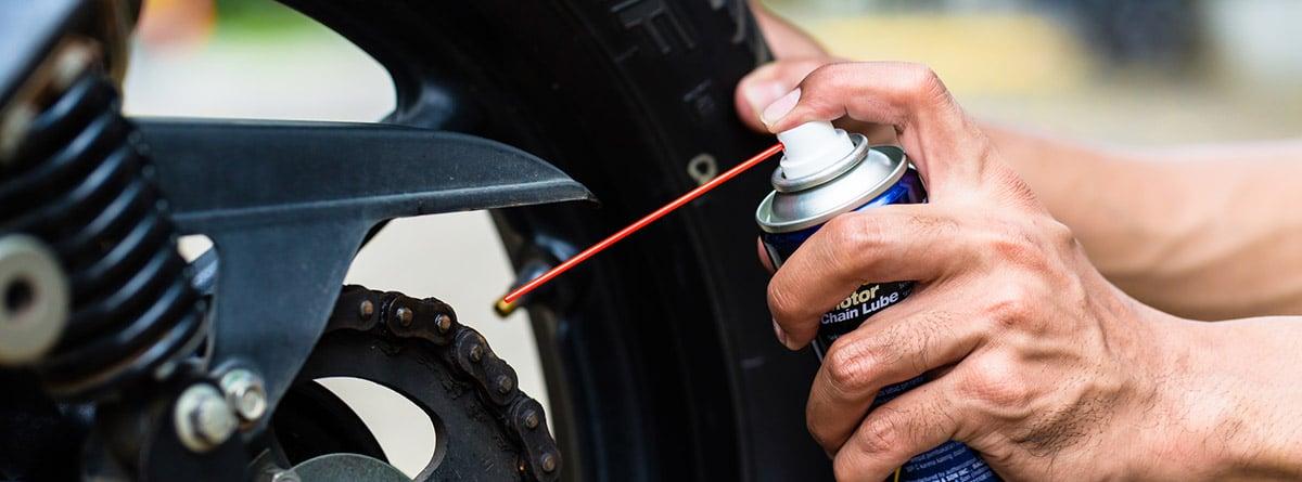 Manos lubricando la cadena de una moto