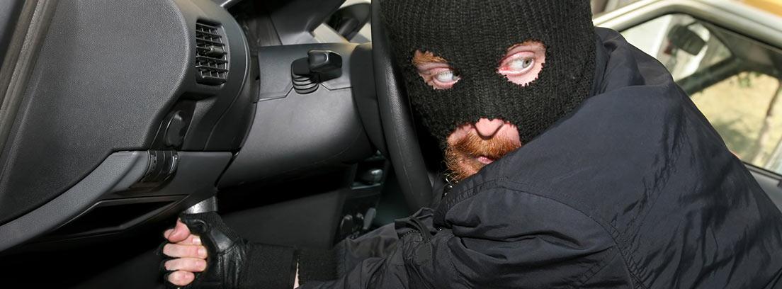 Ladrón con pasamontañas haciendo un puente a un coche