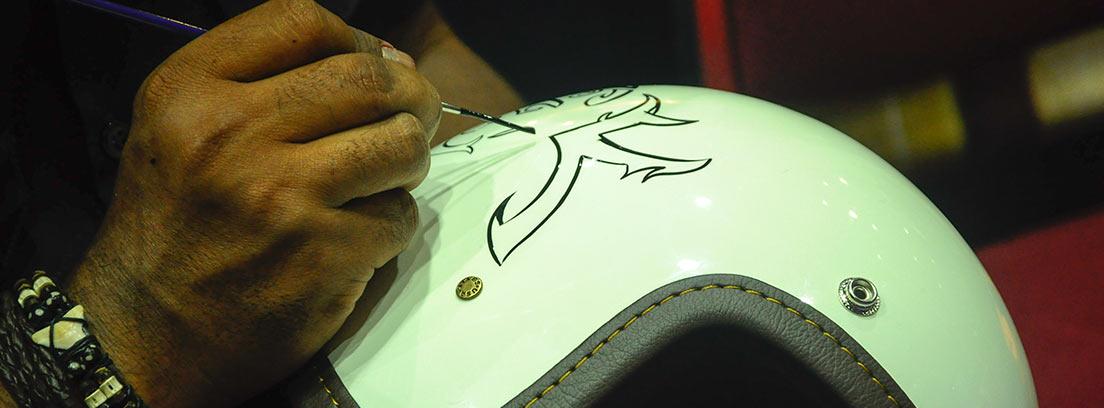 Mano pintando con un pincel sobre un casco blanco