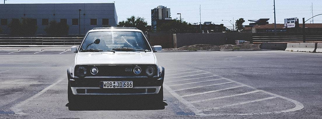 Coche blanco Golf GTI aparcado en parking vacío