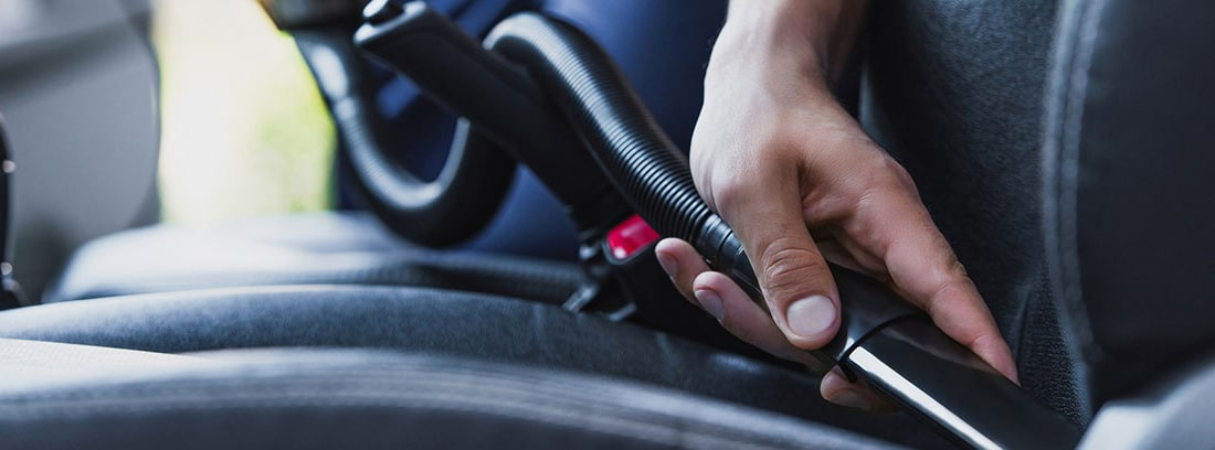 Manos utilizando una máquina para limpiar el interior de un coche