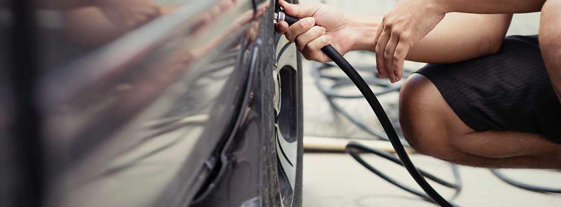Hombre hinchando la rueda de un coche