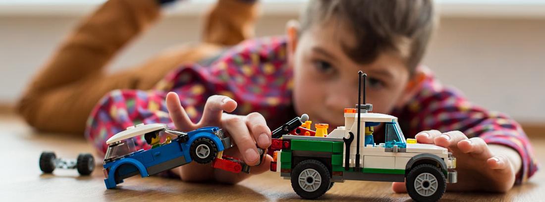 Niño tumbado en el suelo jugando con una grúa y un coche de juguete