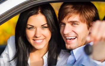 Hombre y mujer sonrientes dentro de un coche mostrando las llaves
