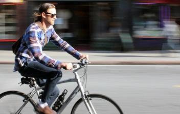 Hombre circulando en una bici por una ciudad