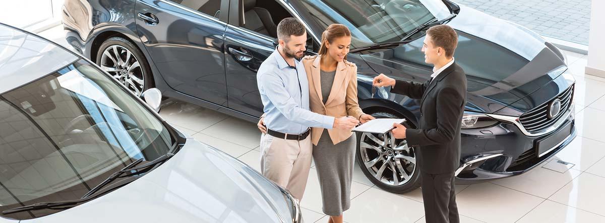 Pareja y vendedor en un concesionario de coches