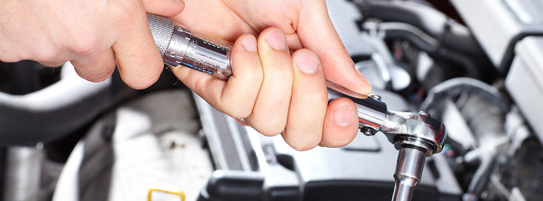 mano de un mecánico cambiando piezas en un coche