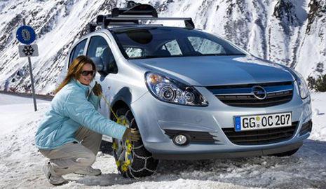 mujer colocando las cadenas en un coche sobre la nieve