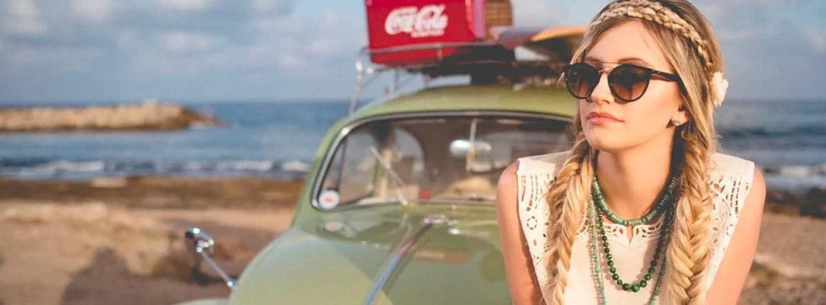 Mujer sentada en el capó de un coche Escarabajo