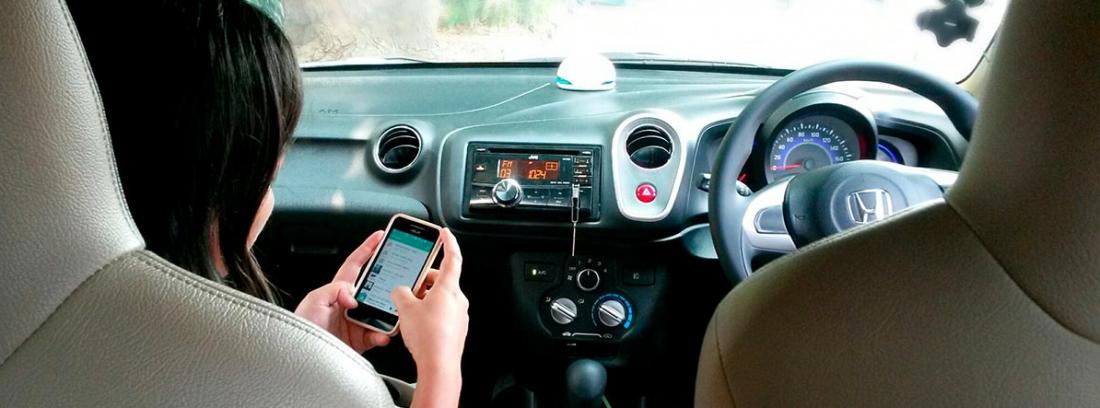 Mujer dentro de un coche consultando en el móvil apps para comprar coche