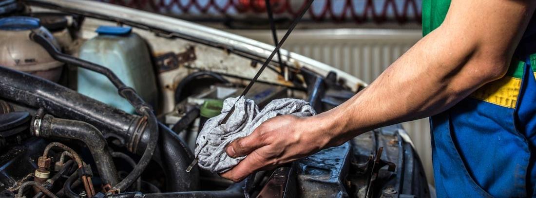 Mano sujeta trapo y varilla de aceite delante de motor de coche