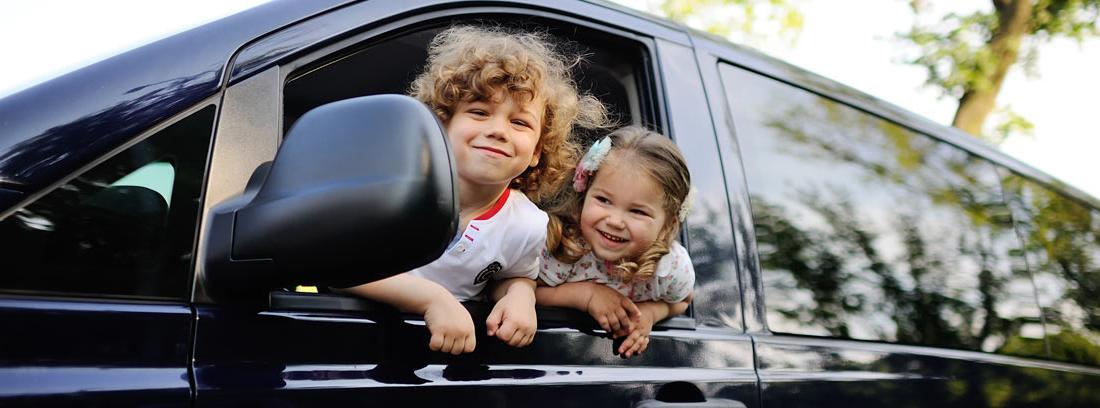 Dos niños sonrientes asomados por la ventanilla de un monovolumen por menos de 20.000 euros