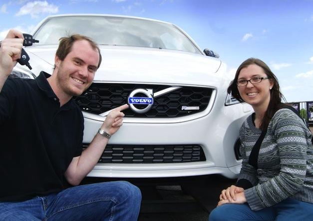 una pareja donde el chico señala un coche Volvo con dos llaves de coche en la mano