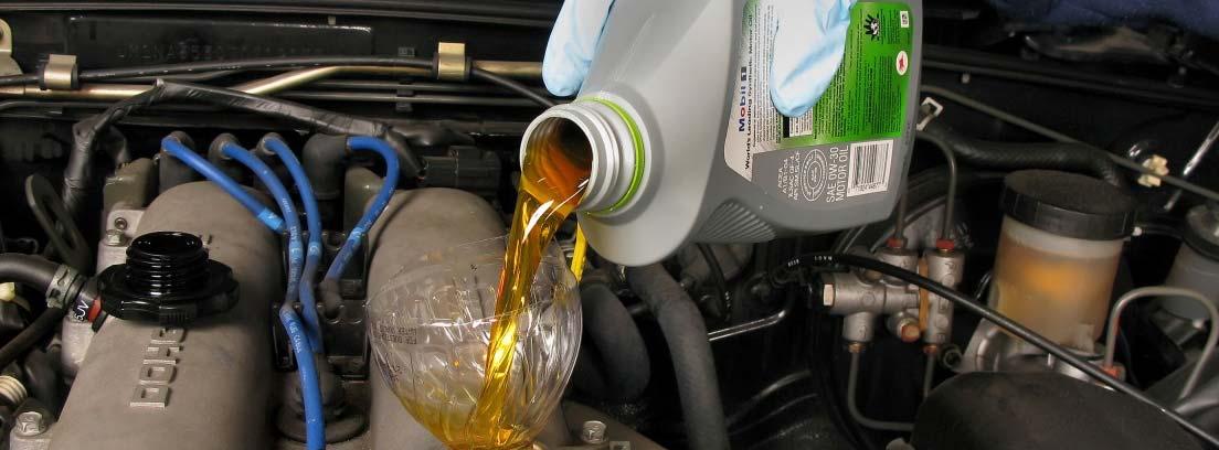 Manos vertiendo aceite en el depósito de un coche
