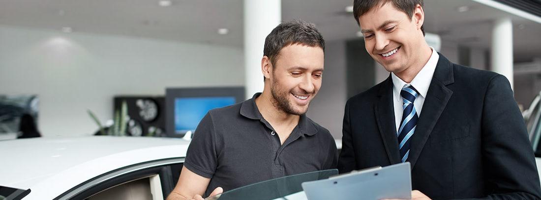 Dos hombres hablando frente a un coche nuevo