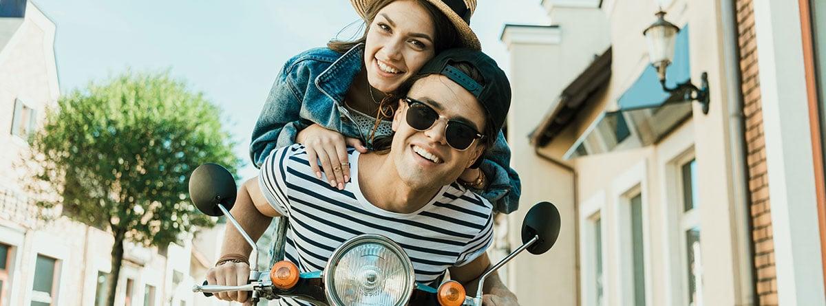 Pareja sonriente sobre una scooter