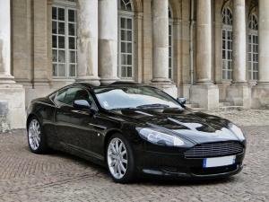 Aston Martin DB9 negro frente a edificio con pilares