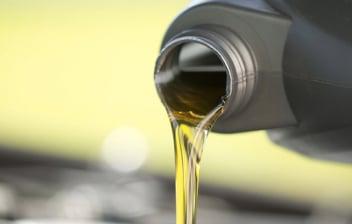 Mano vertiendo aceite de una botella