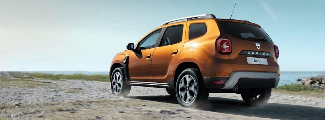 Dacia Duster naranja circulando por un camino