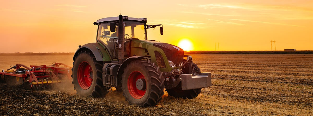 Tractor rojo con arado en una puesta de sol