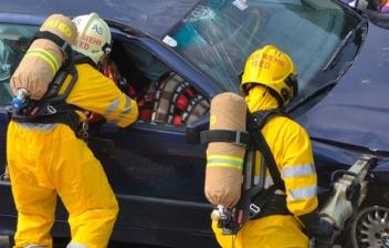 Diferentes profesionales con monos amarillos rodean un coche siniestrado.