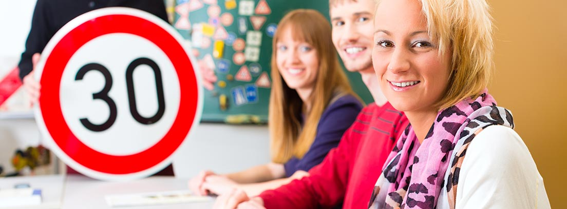 Varias personas sentadas en una mesa al lado una señal de tráfico y un profesor
