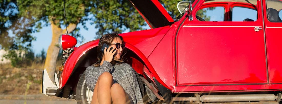 Mujer hablando por teléfono junto a un coche antiguo con el capó abierto