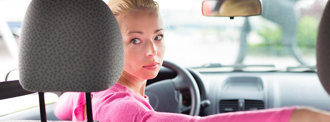 Mujer al volante apoya brazo en asiento copiloto y mira hacia atrás.