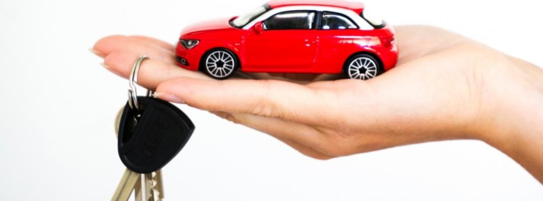 Mano sosteniendo unas llaves y la miniatura de un coche rojo