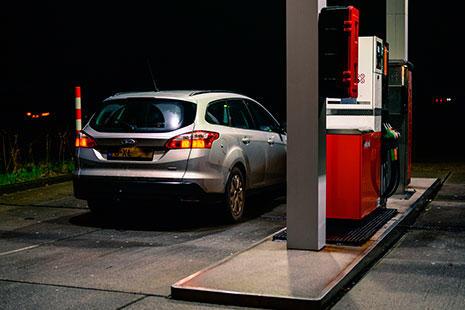 un coche monovolumen parado en una gasolinera