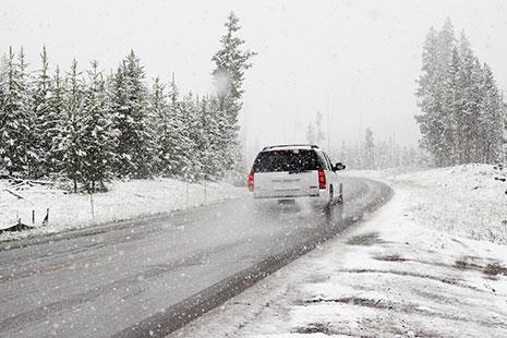 4x4 blanco en marcha sobre carretera y paisaje nevado y nevando