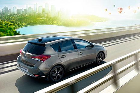 Toyota Auris Hibrido gris en marcha sobre un puente