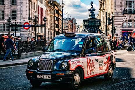 Taxi de Londres pasando por Picadilly Circus