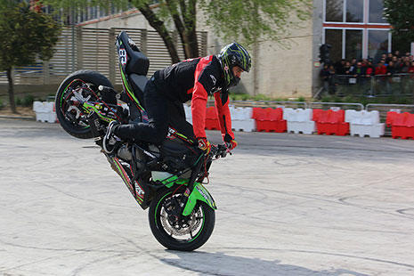 Conductor con una moto negra y verde hace un caballito con la rueda delantera.