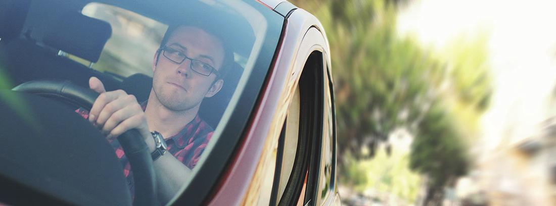 hombre conduciendo mirando nervioso a atrás