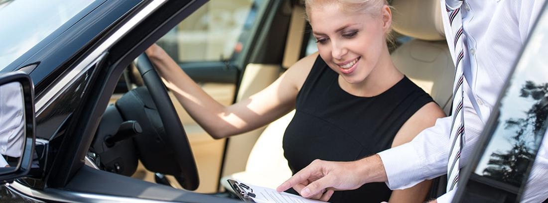 Mujer sentada al volante coche mira papel que le muestra hombre fuera.